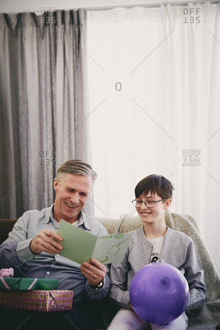 Smiling grandfather reading greeting card while sitting with grandson and gifts at party in living room