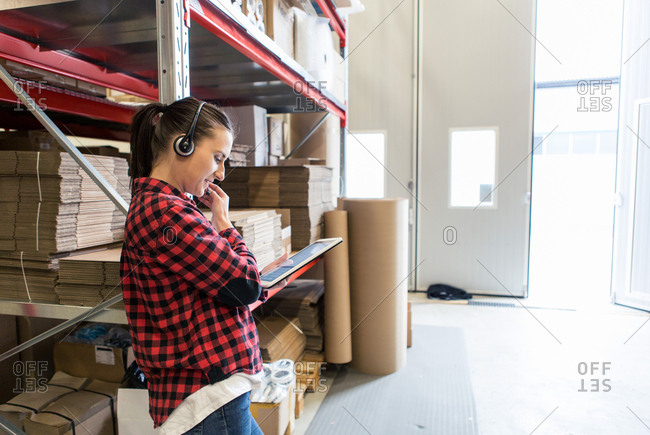 Determined female manual worker wearing headphones while using digital tablet at warehouse
