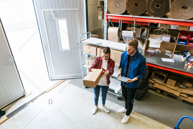 High angle view of male and female coworkers examining cardboard box at distribution warehouse