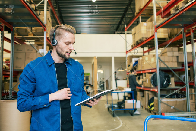 Confident manual worker wearing headphones while using digital tablet in warehouse