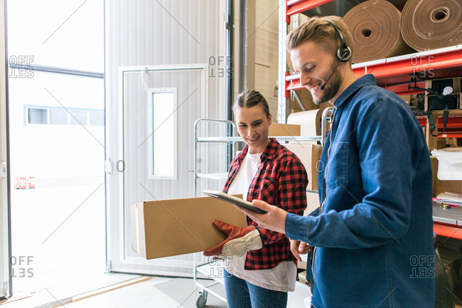 Smiling man showing digital tablet to female coworker holding box in distribution warehouse