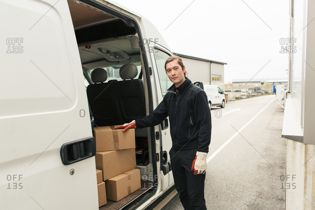 Confident manual worker standing by stack of boxes in delivery van