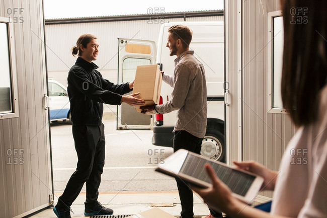 Female using digital tablet while male coworkers delivering boxes in van
