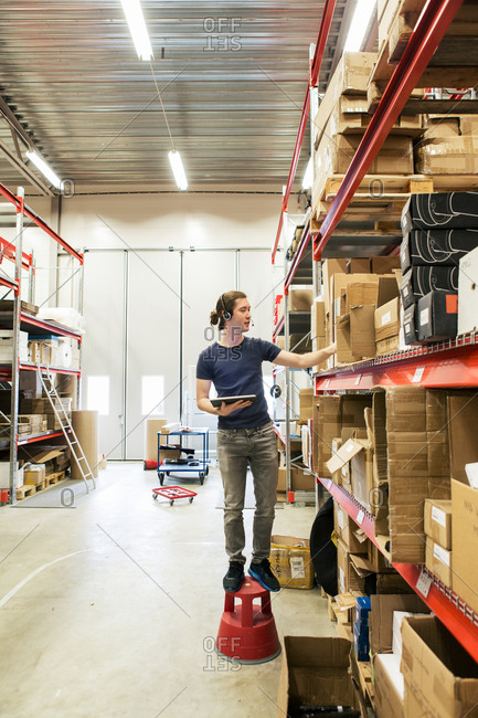 Manual worker analyzing boxes while using digital tablet in distribution warehouse
