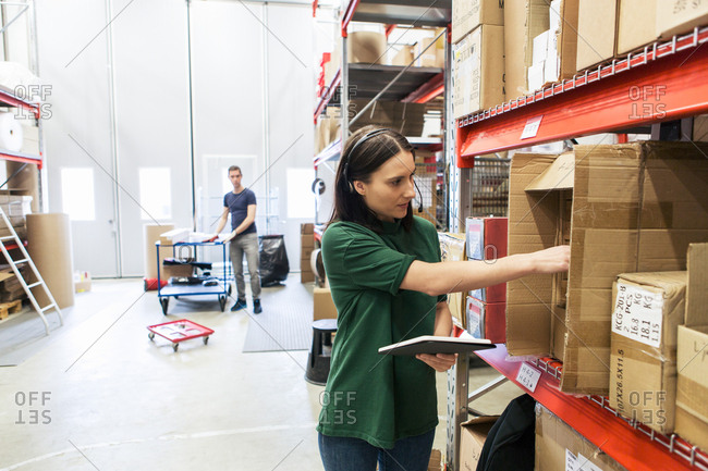 Male and female colleagues examining boxes in industry