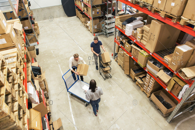 High angle view of coworkers working together in distribution warehouse