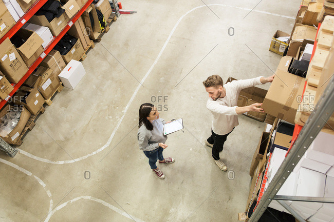 Colleagues discussing while examining cardboard boxes in industry