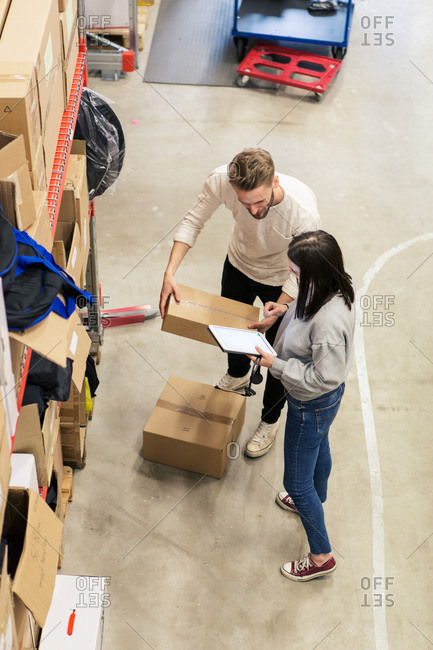 High angle view of colleagues discussing over cardboard box in industry