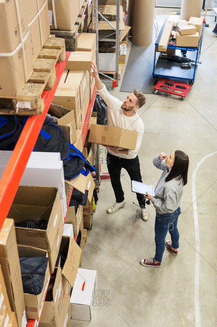 High angle view of colleagues examining boxes in industry