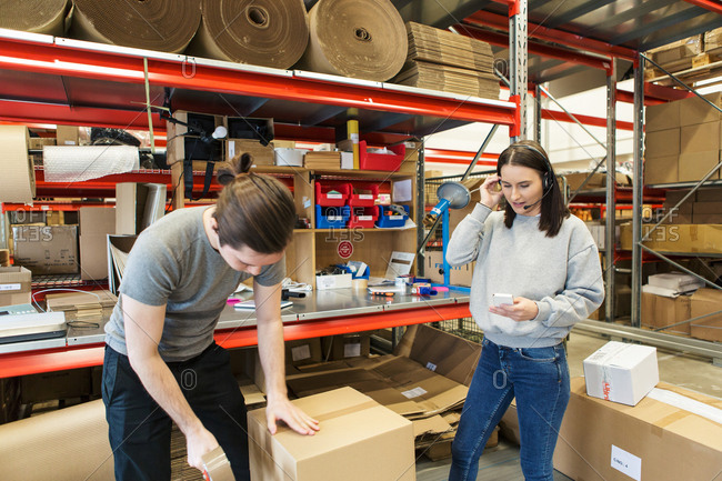 Woman using mobile phone while male coworker packing box in warehouse
