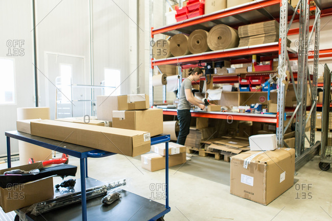 Manual worker packing box in distribution warehouse