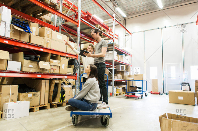 Male and female coworkers examining while standing at warehouse