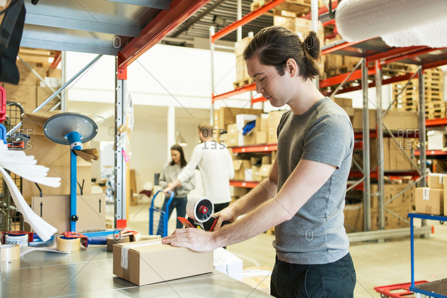 Manual worker packing box while coworkers discussing in distribution warehouse