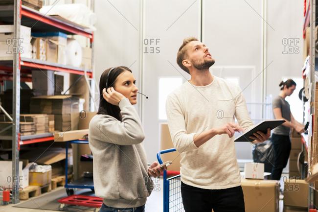 Man and woman examining boxes at distribution warehouse