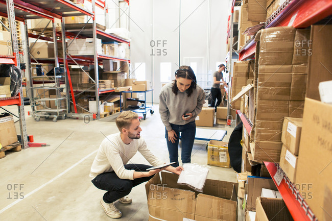 Coworkers examining manufactured objects while using digital tablet at warehouse