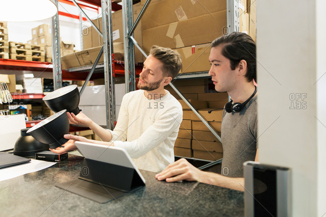 Colleagues discussing over equipment while using digital tablet at industry