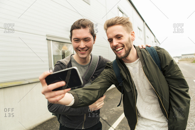 Smiling coworkers taking selfie through mobile phone outside industry