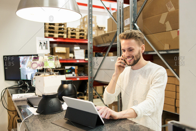 Smiling man talking on mobile phone while using digital tablet in warehouse