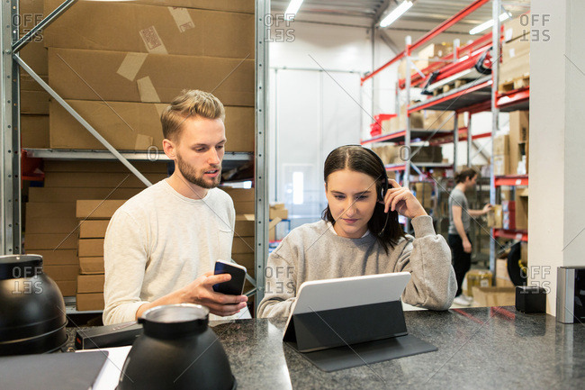 Colleagues discussing over digital tablet while standing in warehouse