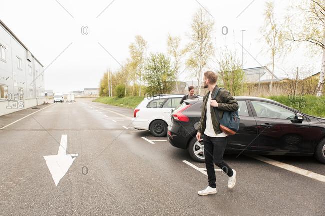 Men walking by cars on road in city against sky