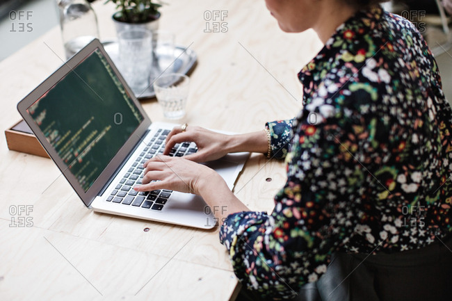 Midsection of businesswoman using laptop at table in office