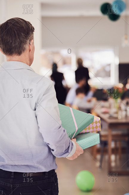 Rear view of senior man holding gift boxes at home