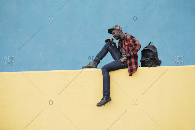 Handsome black man with cap using the mobile sitting on a wall, wearing casual clothing