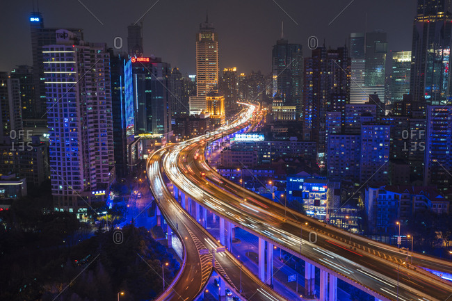 Shanghai, China - March 26, 2016: Elevated view of stacked road junction and skyline at dusk