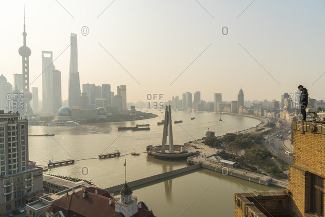 Shanghai, China - March 26, 2016: Man admiring view over Huangpu River and skyline in early morning