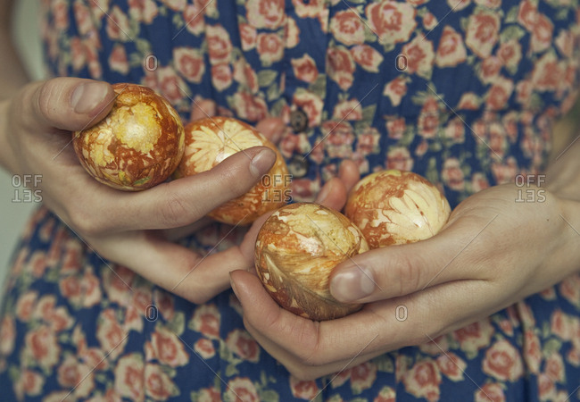 Hands holding easter eggs dyed with onion shells
