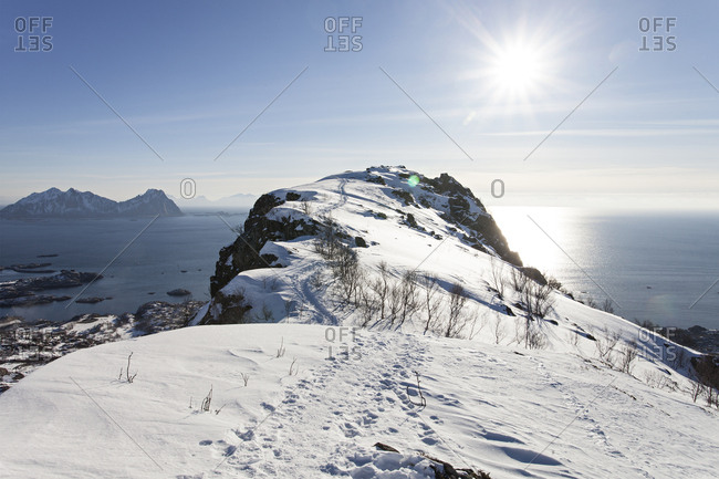 Sun flare over ocean in snowy Norway