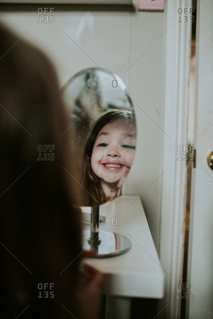 Cute girl admiring lipstick on face in the mirror