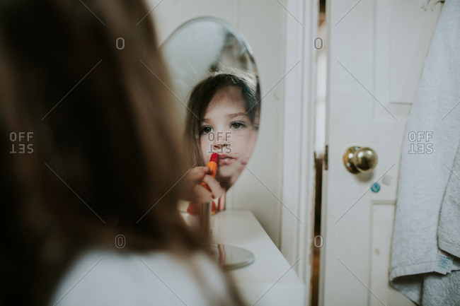 Young girl trying on lipstick at bedroom vanity stand