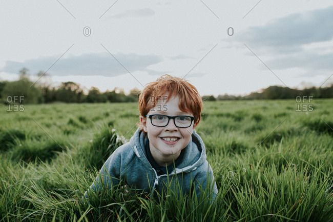 Happy adolescent boy in glasses posing in grassy field