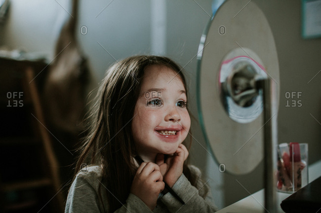 Sweet little girl admiring messy lipstick in bedroom mirror