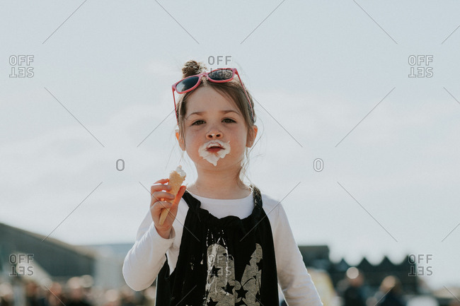Cute brunette girl with sunglasses eating sticky ice cream cone outside
