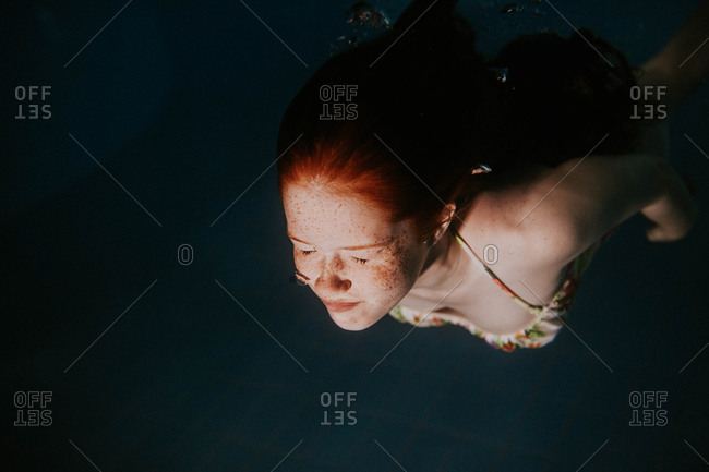 Underwater view of redhead teen swimming with eyes closed
