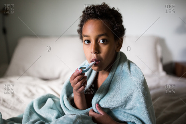 Sick girl sitting in bed wrapped in blanket checking temperature
