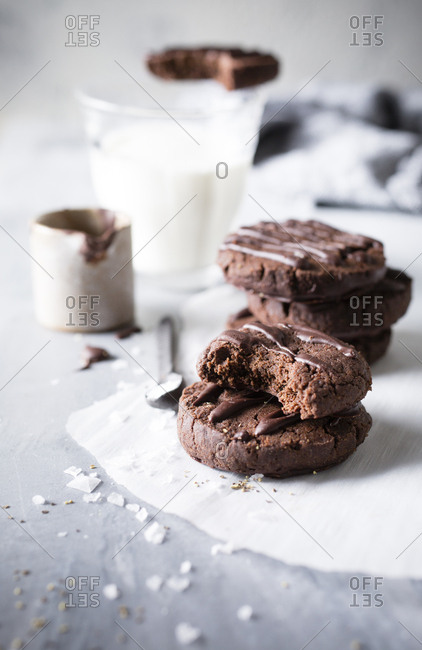 Crumbs around half eaten stack of Chocolate sables cookies served with glass of milk
