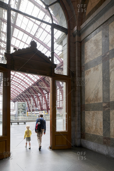 Antwerp, Belgium - June 13, 2018: Father and daughter walking through doors to train hall of Antwerpen-Centraal railway station, built in the eclectic style by architects Louis Delacenserie and Charles Poupaert