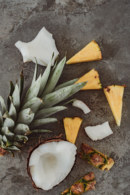 Top down view of wedges of pineapple and pieces of broken coconut