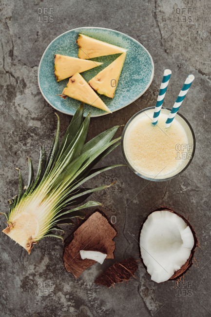 Top down view of coconut and pineapple smoothie arranged with chunks of coconut in the shell and sliced pineapple