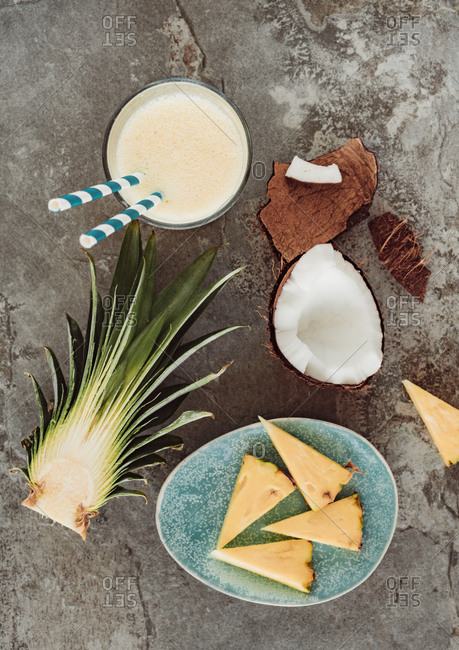 Overhead view of coconut and pineapple smoothie surrounded by pineapple chunks and coconut