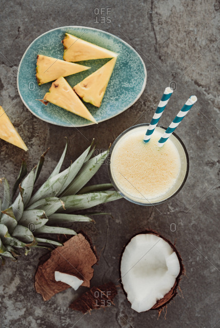 Top down view of chunks of coconut in the shell and sliced  arranged with pineapple coconut and pineapple smoothie