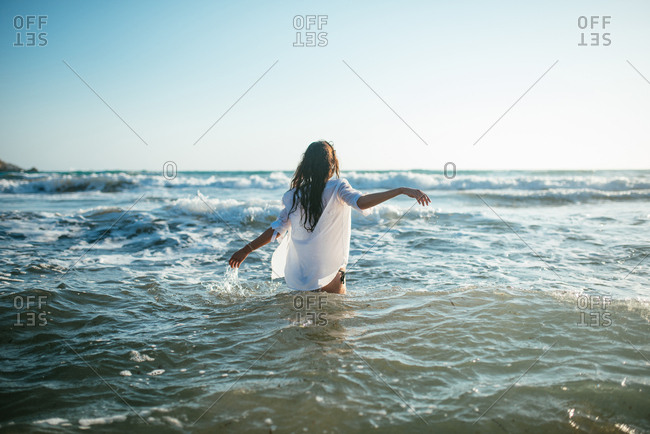 Attractive young woman with wet white shirt walking in the sea