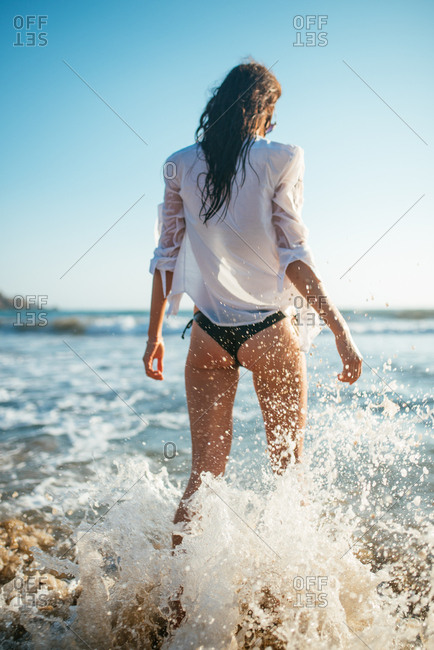 Young woman walking in the sea with wet white shirt on