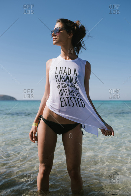 Young woman with white t-shirt walks in the sea