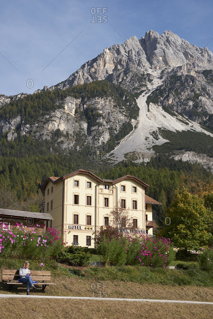 Vodo di Cadore, Italy - October 13, 2017: Hotel with mountain peak and tourist in the Italian dolomites