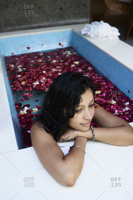 Asian woman looking away while having a relaxing bath with petals in spa at home