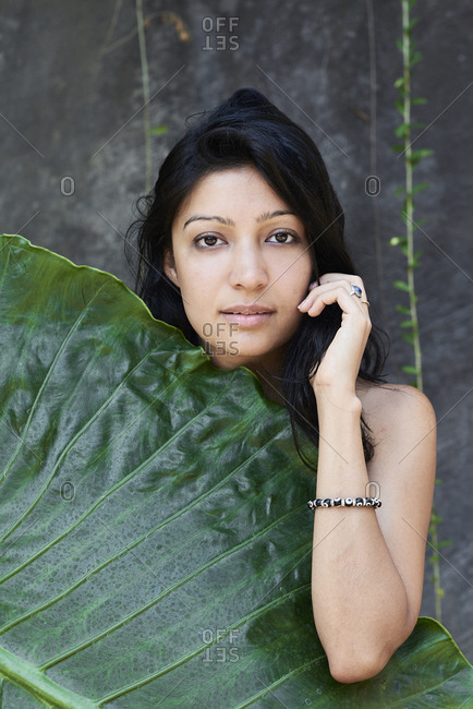 Portrait of nude brunette Asian woman covered by tropical leaf